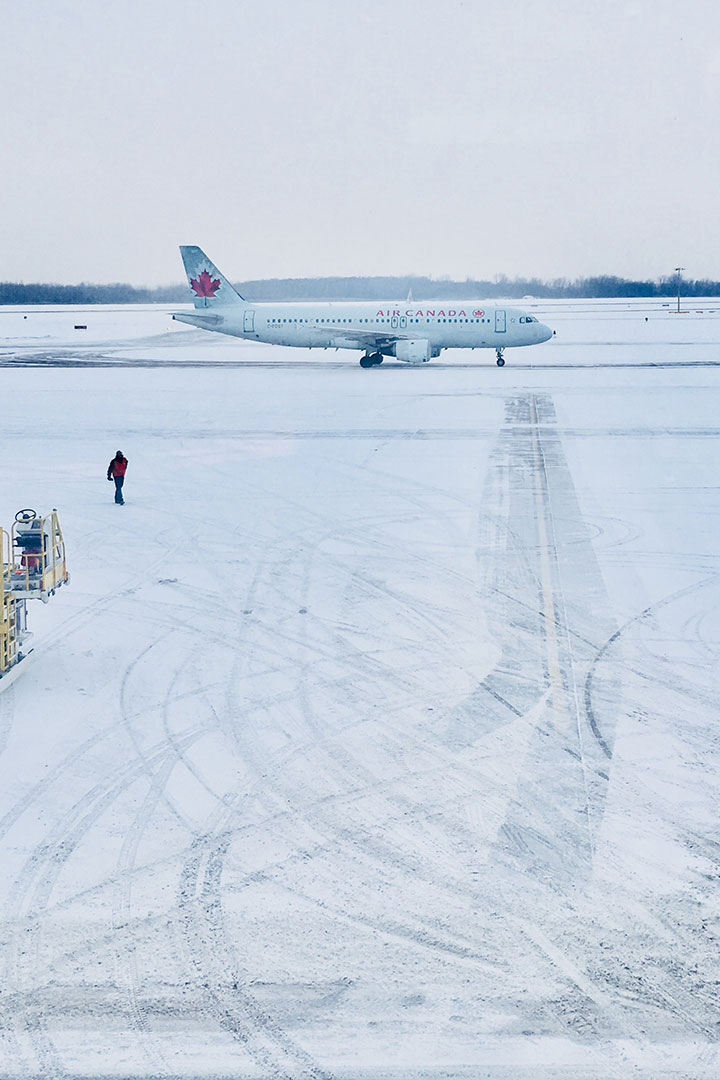 An Air Canada plane on a snowy runway