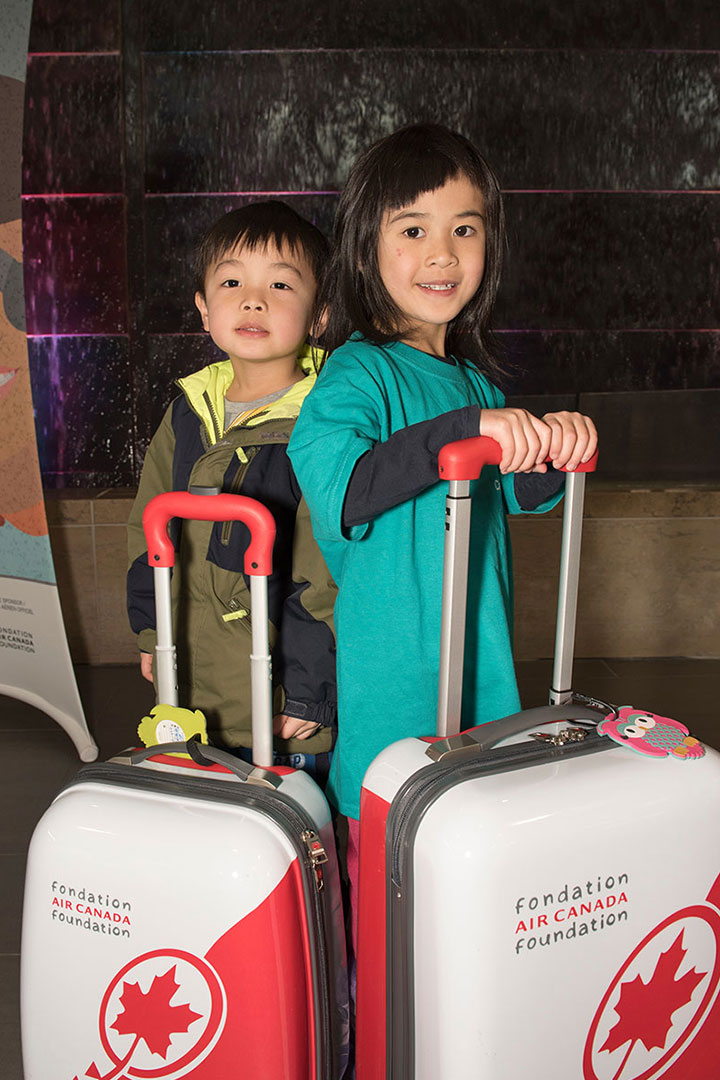 Two kids with Air Canada suitcases