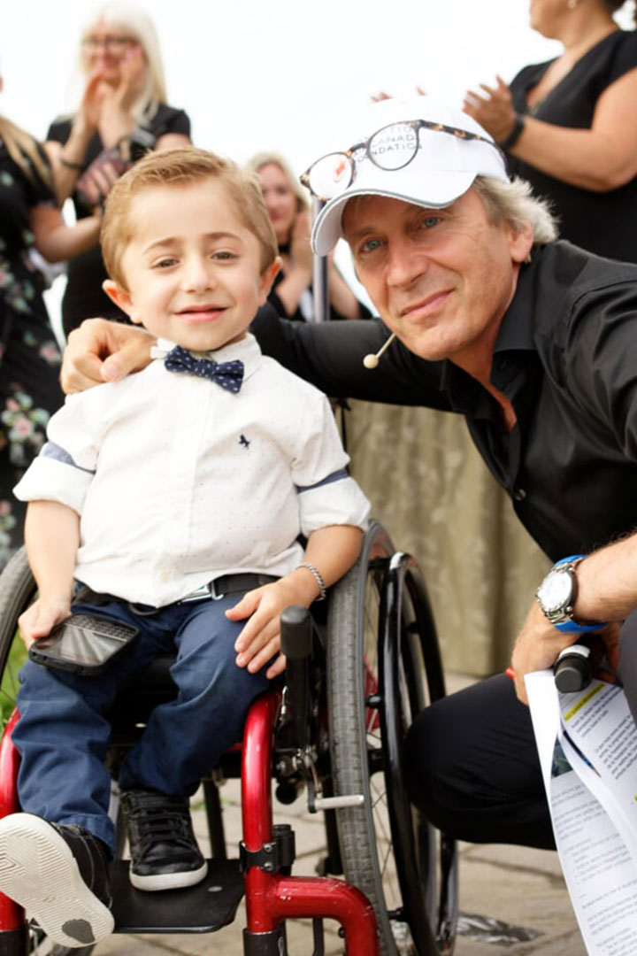 Boy in wheelchair posing with man