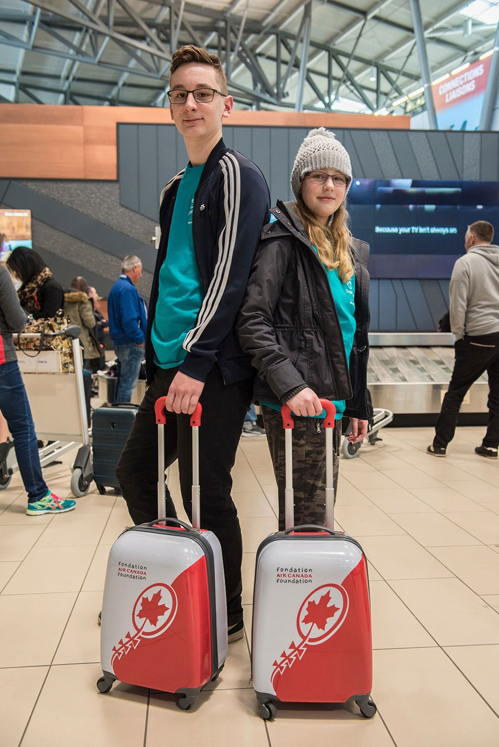 Two teenagers at airport with Air Canada suitcases