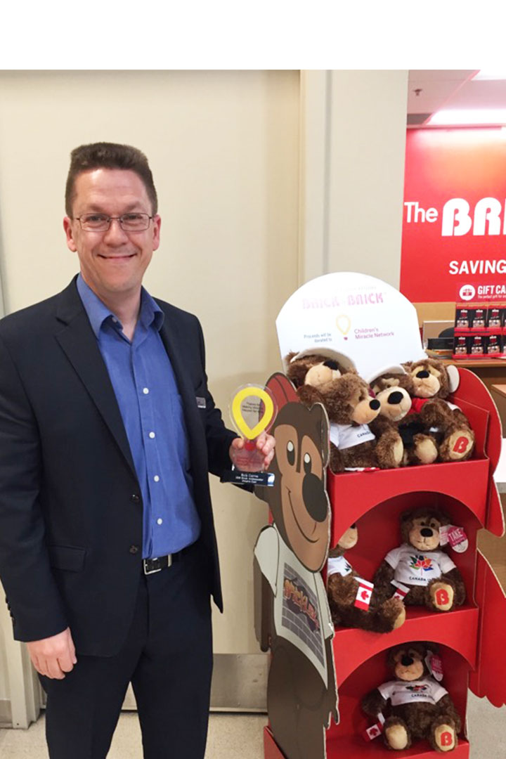 The Brick executive standing next to teddy bear stand