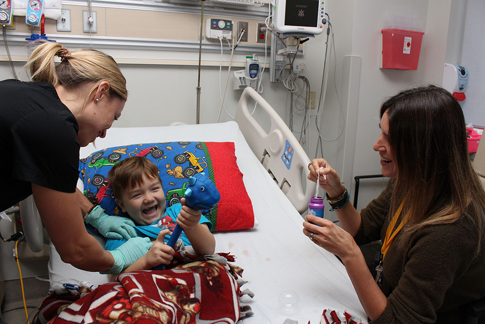 A laughing girl in a hospital being tended to by medical staff and mom
