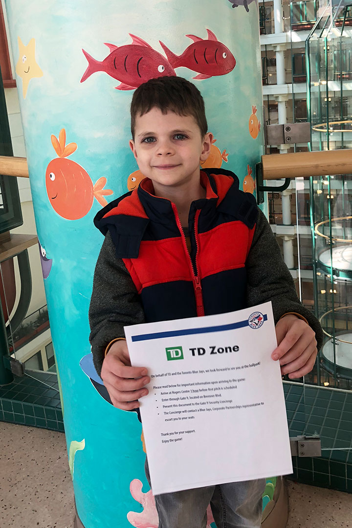 Child holding a TD Zone certificate