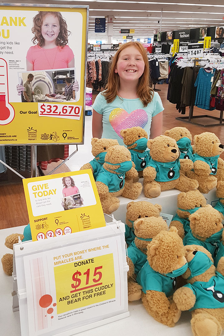 Smiling girl at teddy bear donation booth at Walmart