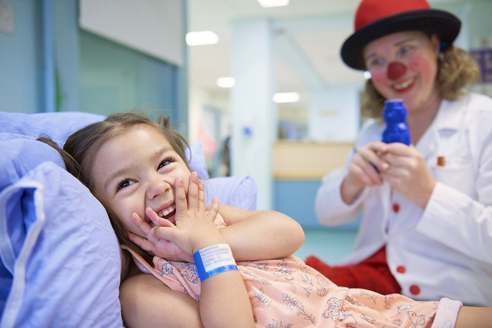 Laughing girl in hospital bed with clown