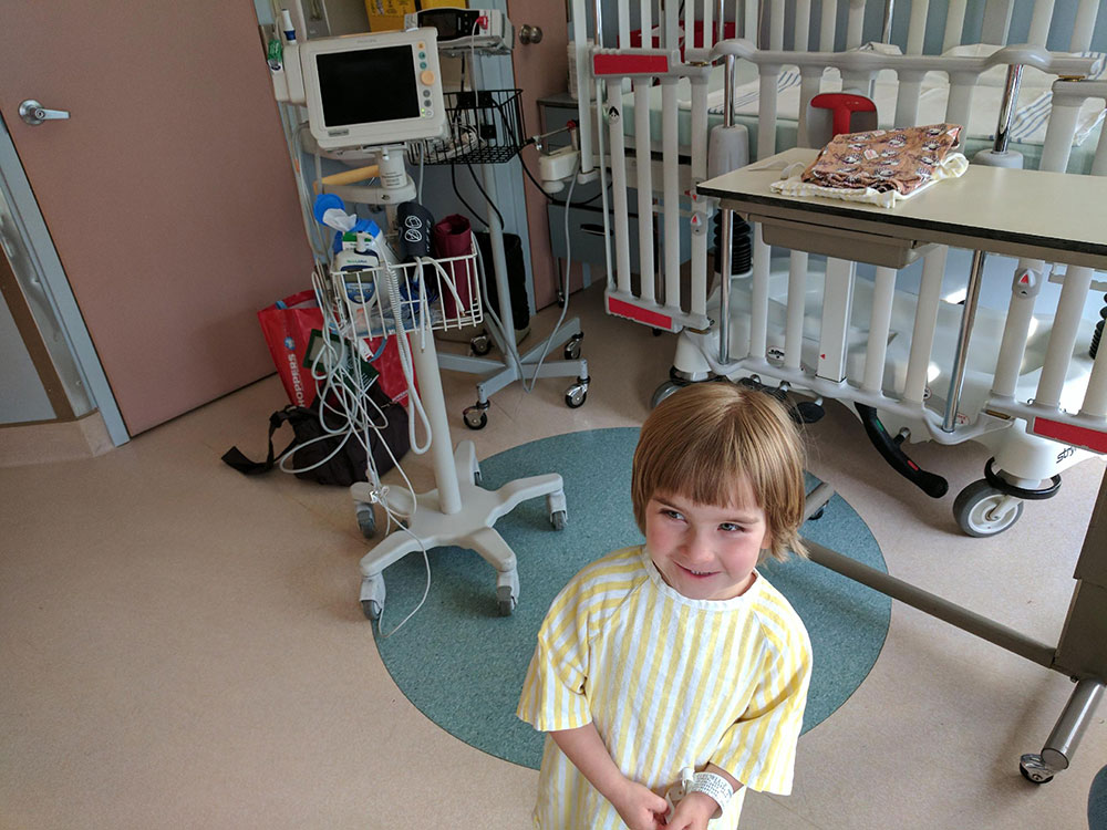 Enfant dressed yellow striped hospital gown in hospital room