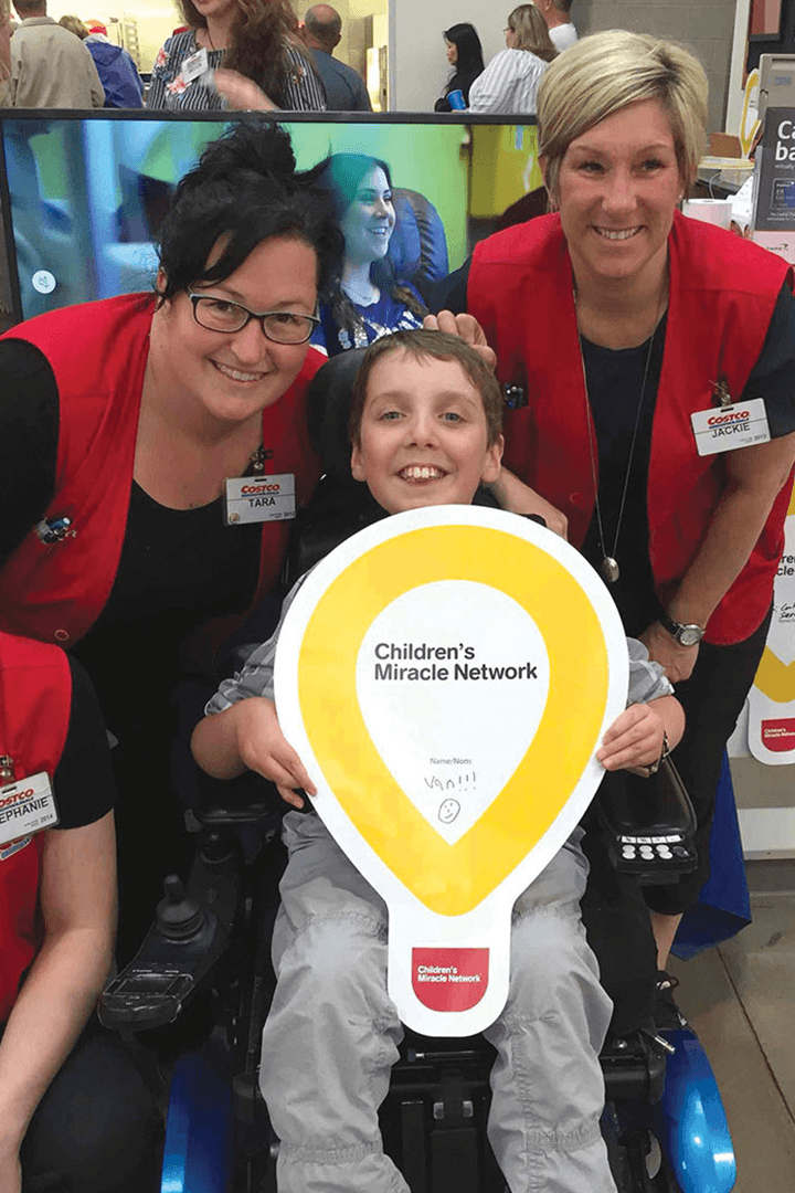 Two Costco team members with a CMN champion
