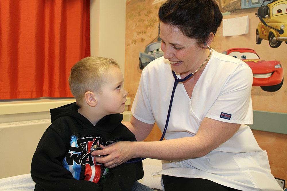 Doctor taking heartbeat of little boy