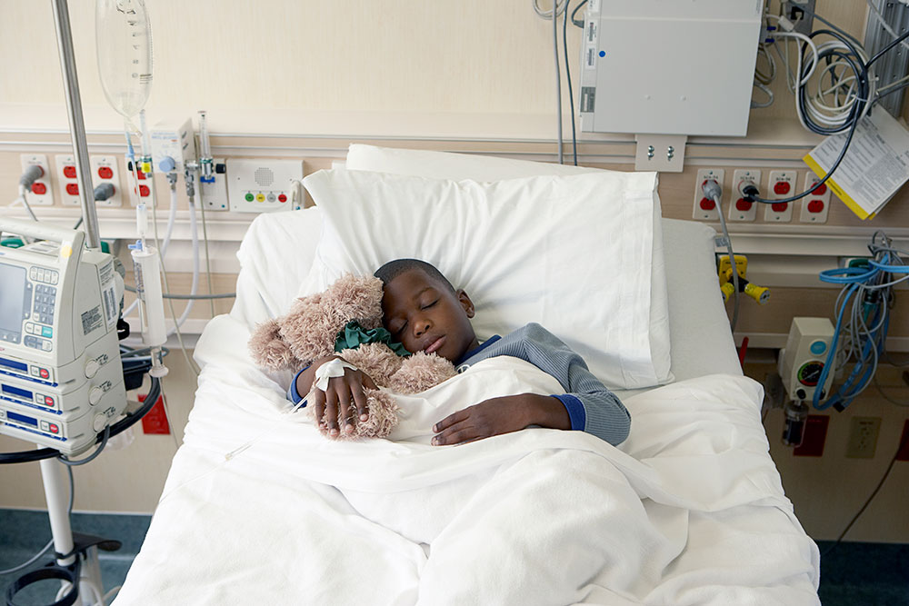 Boy sleeping in hospital bed hugging teddy bear