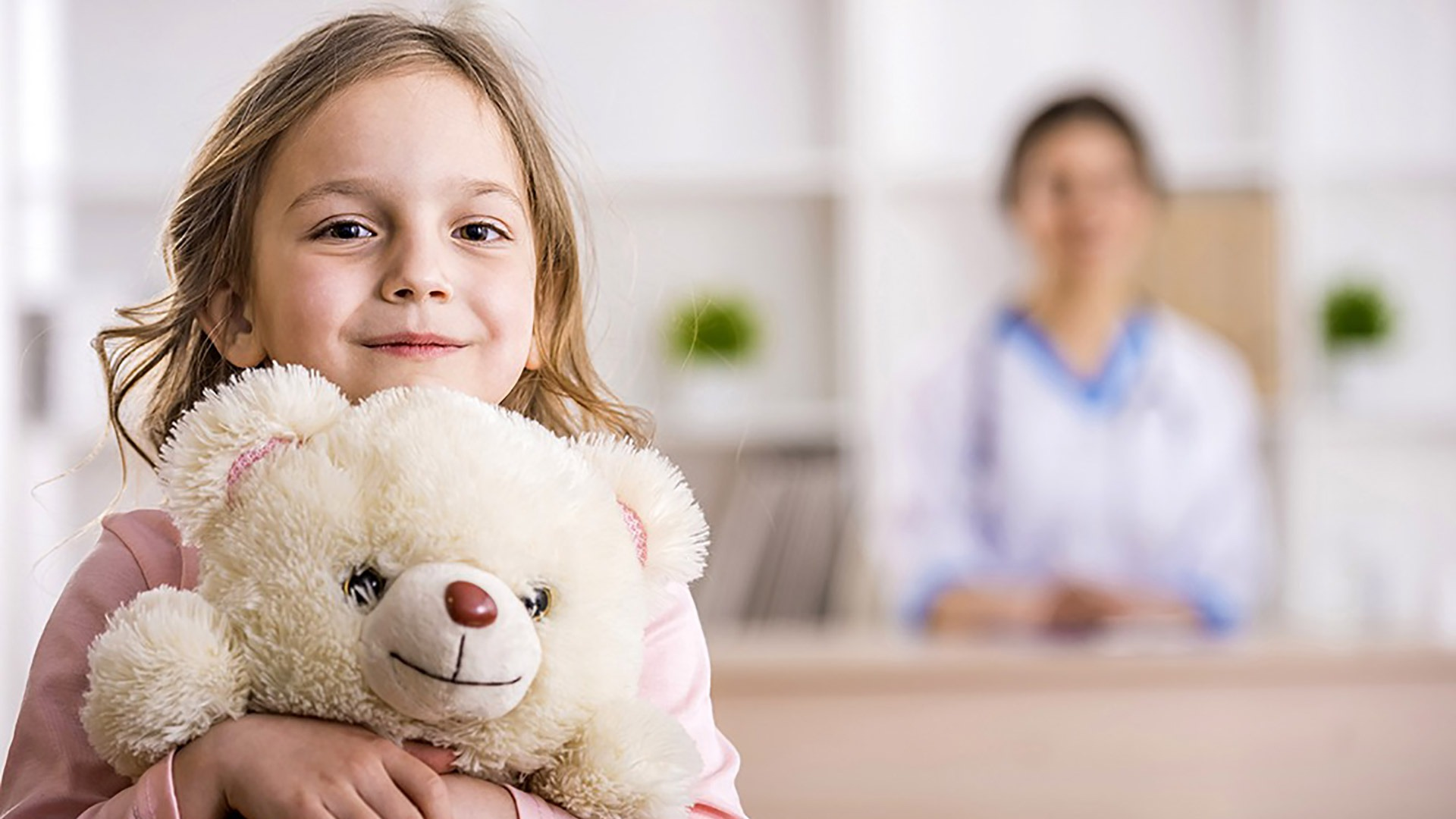 Smiling girl with teddy bear