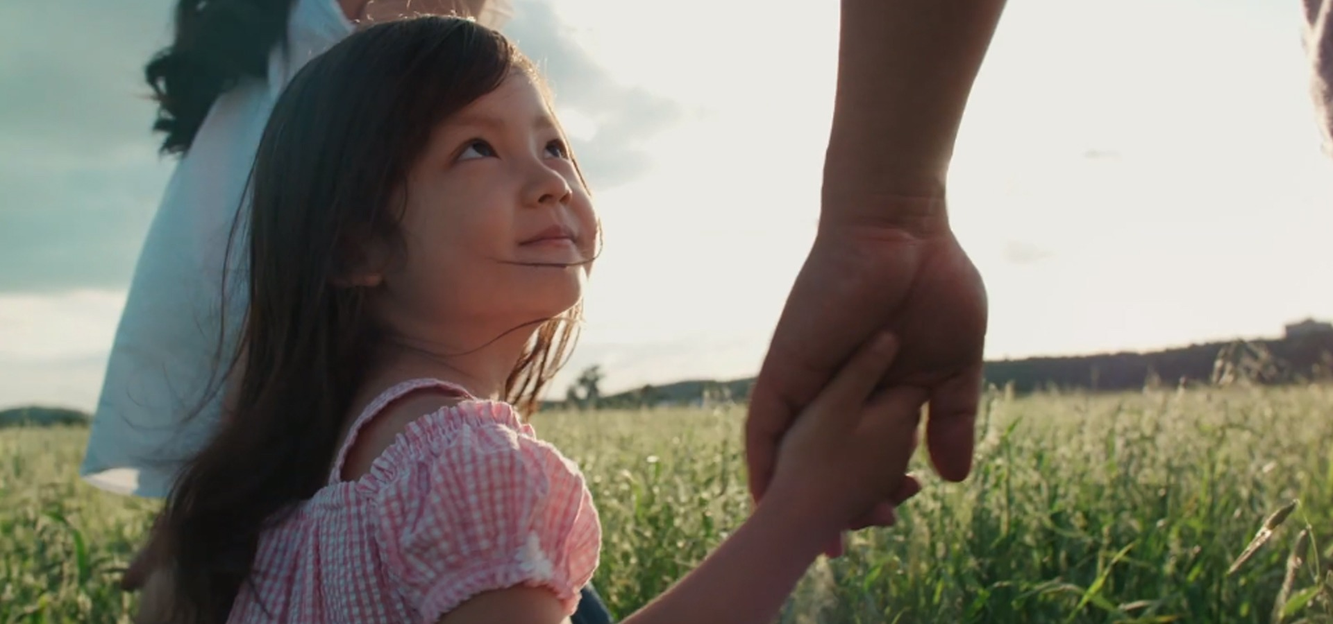 Girl holding hands with parents in field