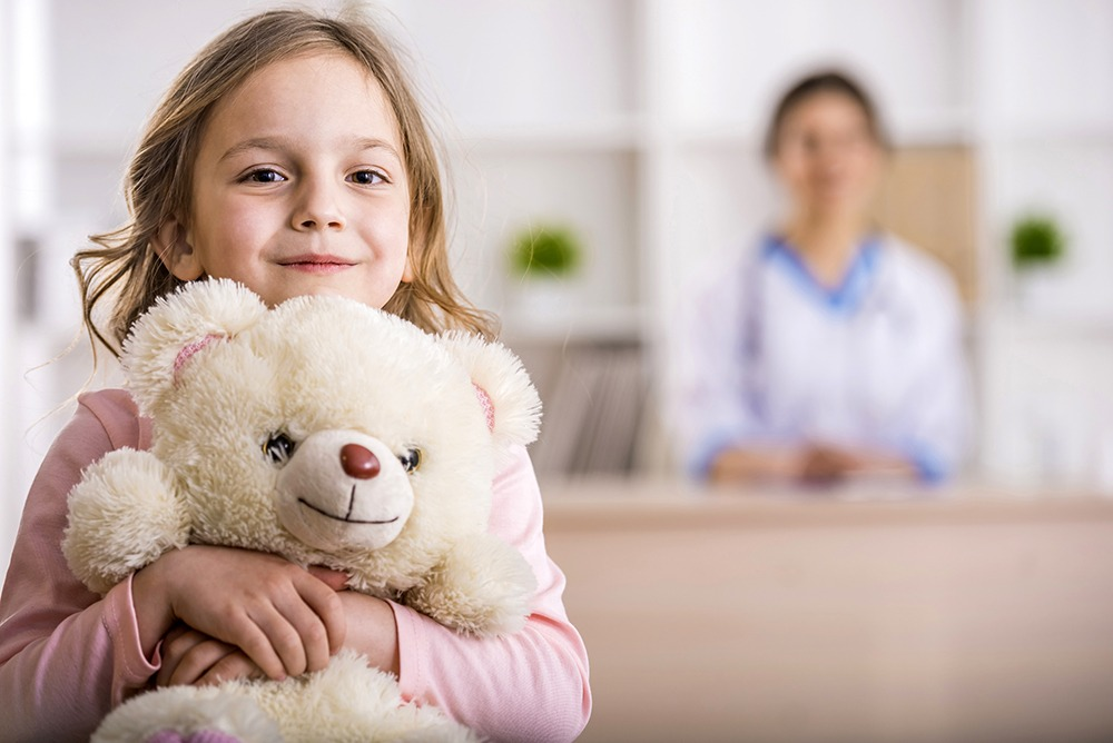 Little girl with teddy bear in front of doctor