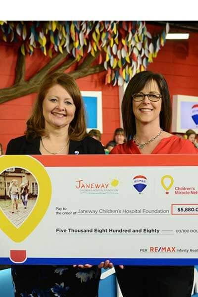 Two women holding a giant Remax / CMN cheque for Janeway Foundations