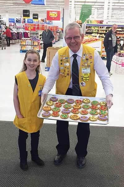 Man and girl holding a tray of happy face cookies