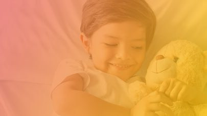 Smiling youth holding teddy bear