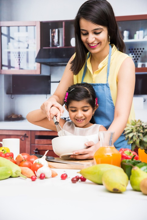 Mother with daughter whisking in the kitchen