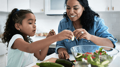 Mother and daughter making nutritious salad