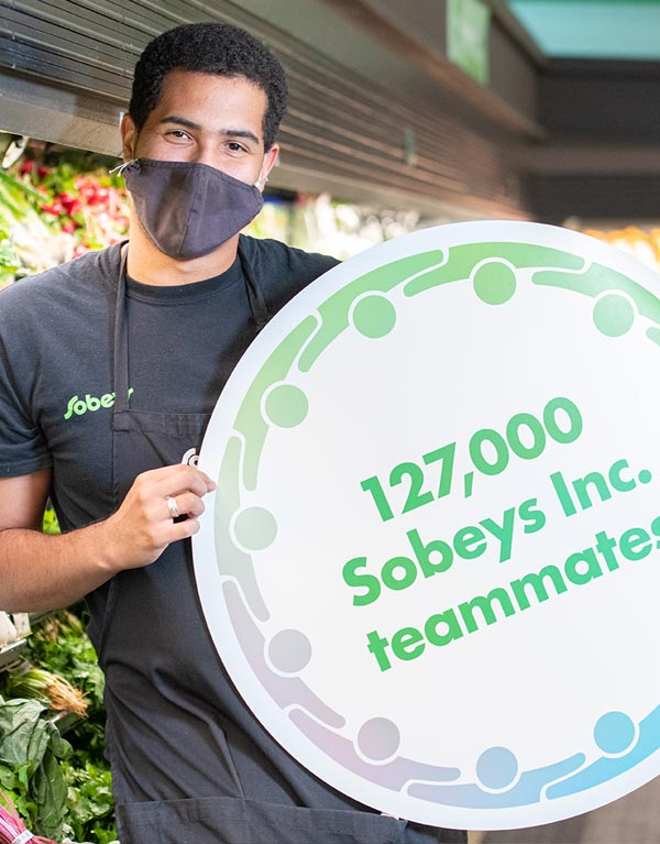 Sobeys team mate holding up signage - 127,000 Sobeys Inc teammates