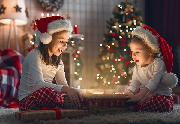 Two girls opening gifts on Christmas Day